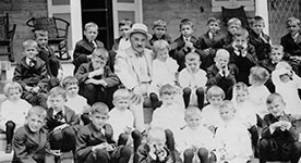 Milton Hershey and boys sitting on steps of Milton Hershey School