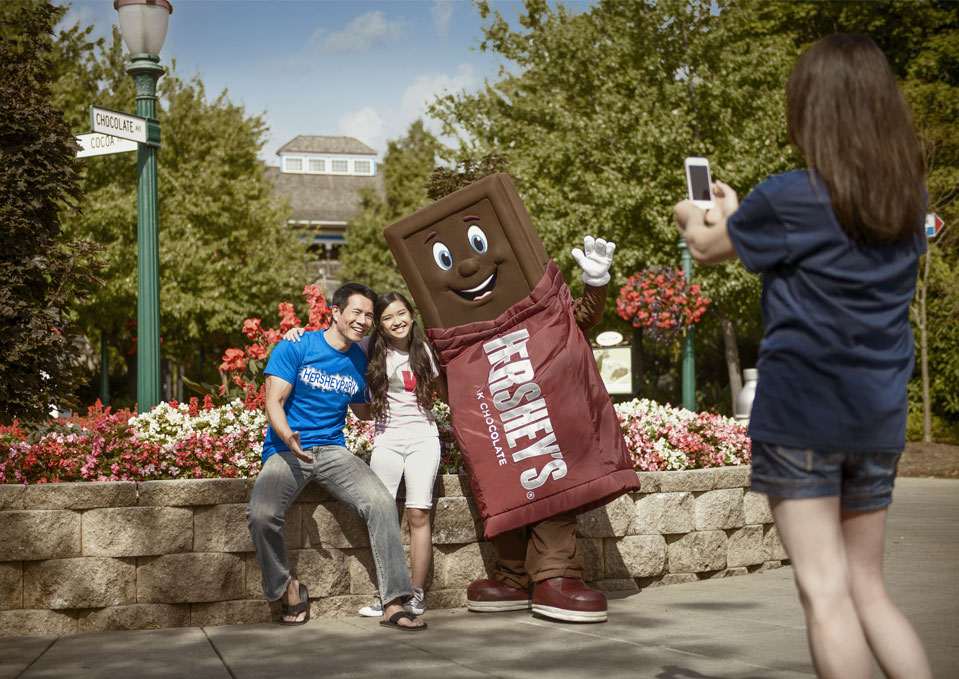 Dad and Daughter taking a photo with Hershey's bar character