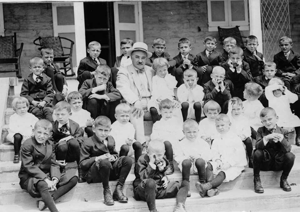 Milton Hershey on the steps with boys from the Milton Hershey School