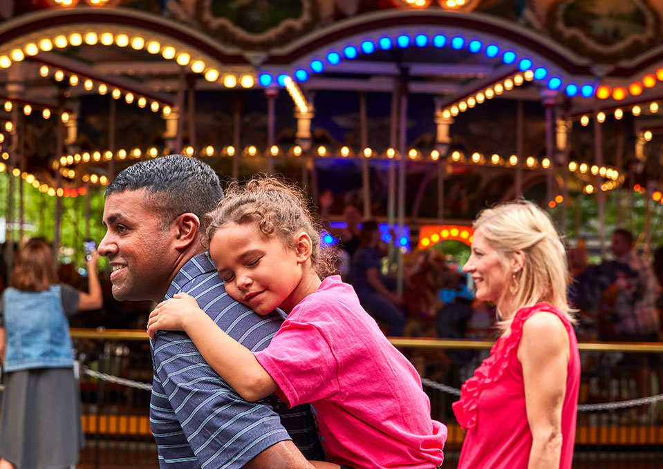 a family walking in front of the Carousel