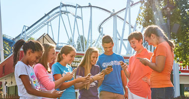 Kids using Hersheypark app next to Great Bear rollercoaster