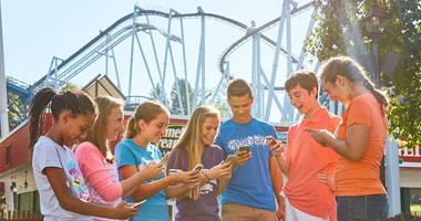 Kids using Hersheypark app next to Great Bear rollercoaster