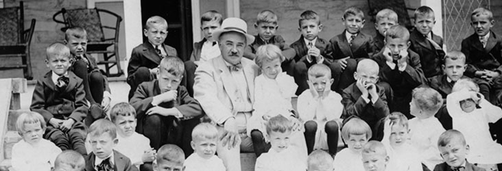 Milton Hershey and boys on the steps of Milton Hershey School