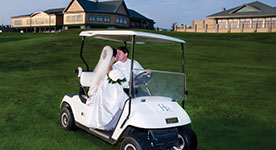 Bride and groom driving away on a golf cart at Hershey Country Club