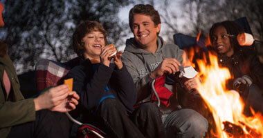 family making smores around a roaring campfire