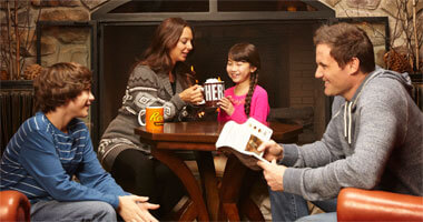 family drinking hot cocoa around fireplace