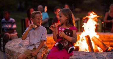 kids eating smores by a campfire