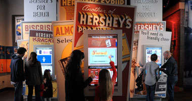 a mother and daughter interacting with an touchscreen kiosk at The Hershey Story museum