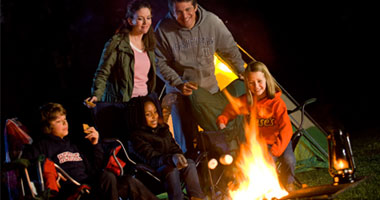 a family at a campfire in Hersheypark Camping resort