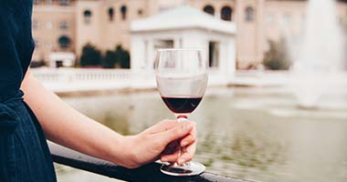 hand holding a glass of wine in front of a fountain