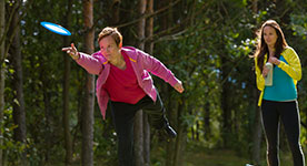 woman throwing a disc at Disc Golf Course