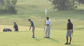 men putting on a golf course