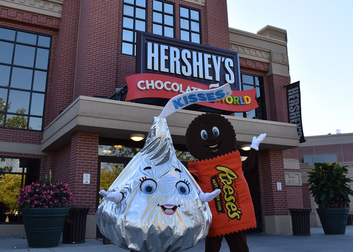 family taking a selfie in front of Hershey's Chocolate World
