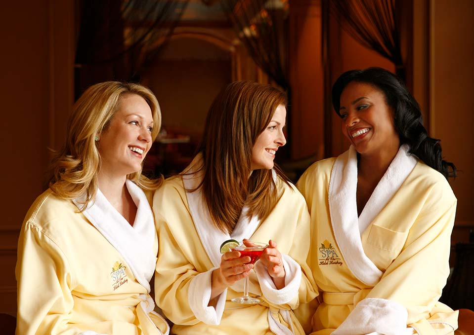 Three women relaxing in robes with martinis