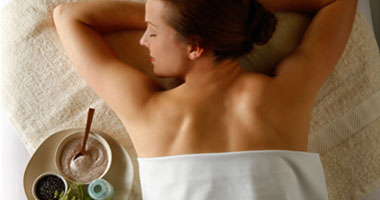 woman laying, waiting for a massage with lotions beside her